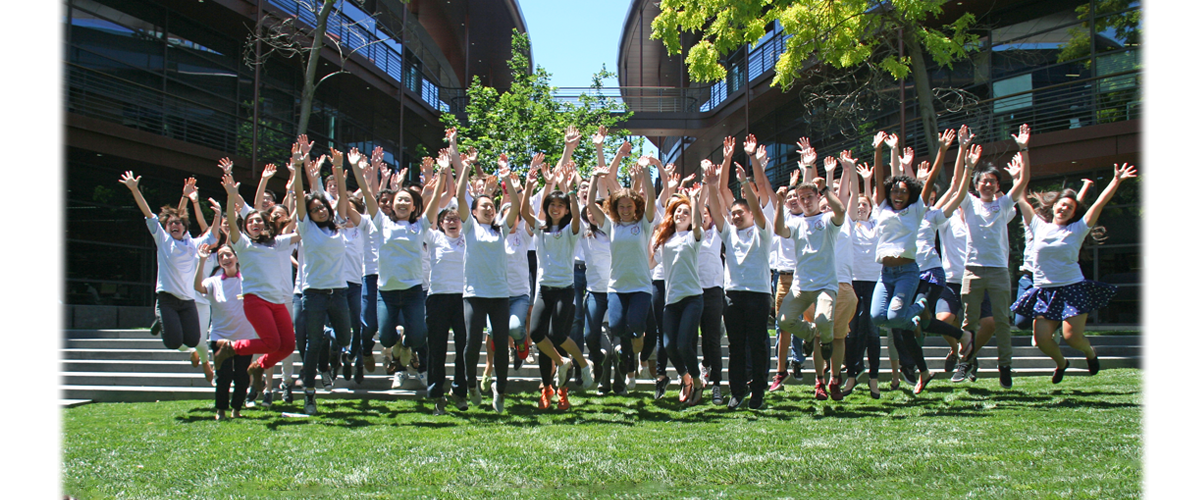 Group photo of 65 undergraduate students jumping in the air on the steps of the Dean's Lawn with the Clark Center building behind them.