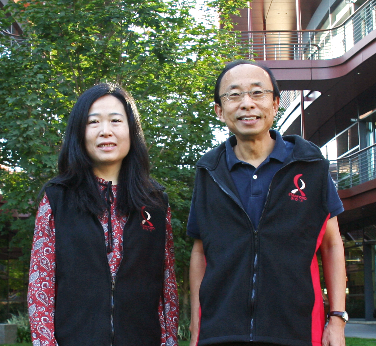 Photo of female Asian faculty member and male Asian faculty member standing side by side at the Clark Center, wearing matching vests with the Bio-X logo.