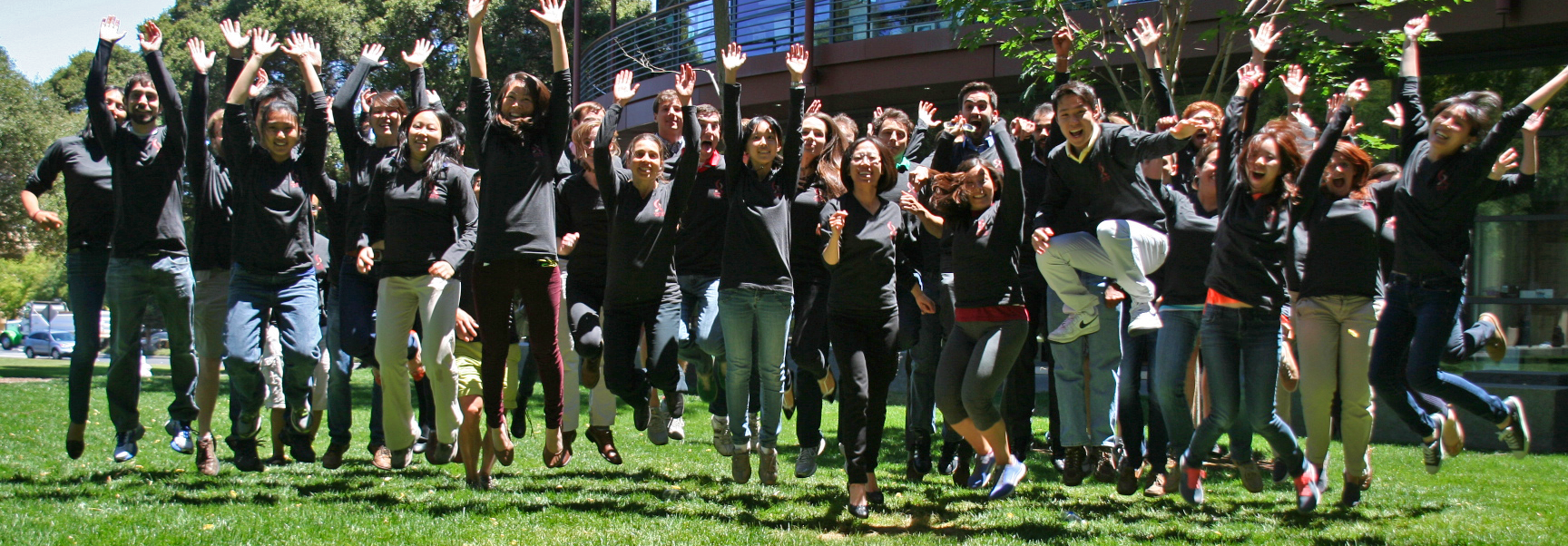 Photo of dozens of Stanford graduate students standing together at the Clark Center wearing matching apparel.