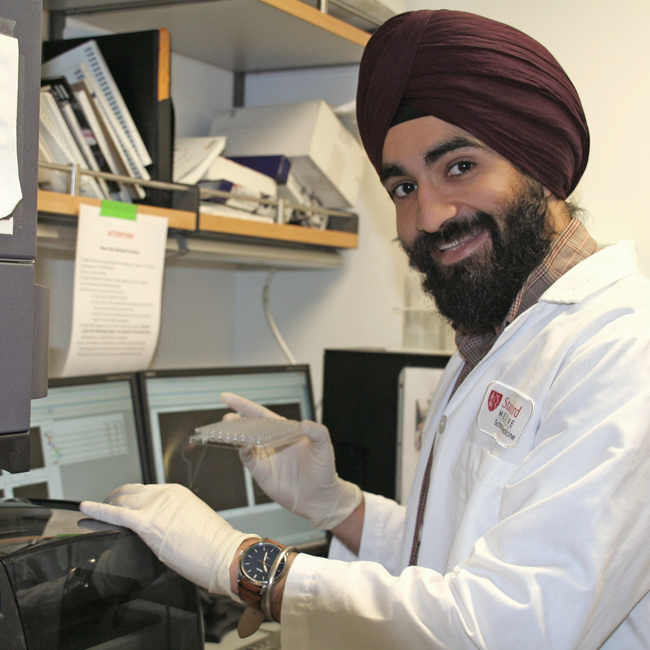 Photo of a male graduate student wearing a turban and working with laboratory equipment, holding up a sample.