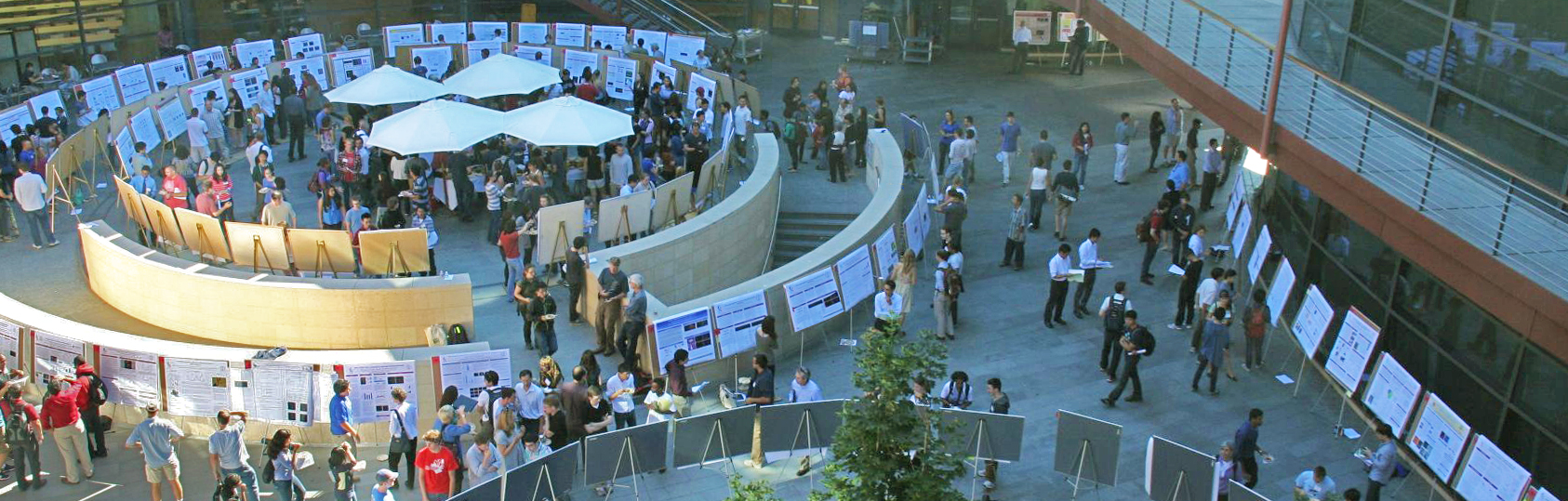 Photo taken from above of the Clark Center, with the courtyard filled with scientific posters and people looking at them.