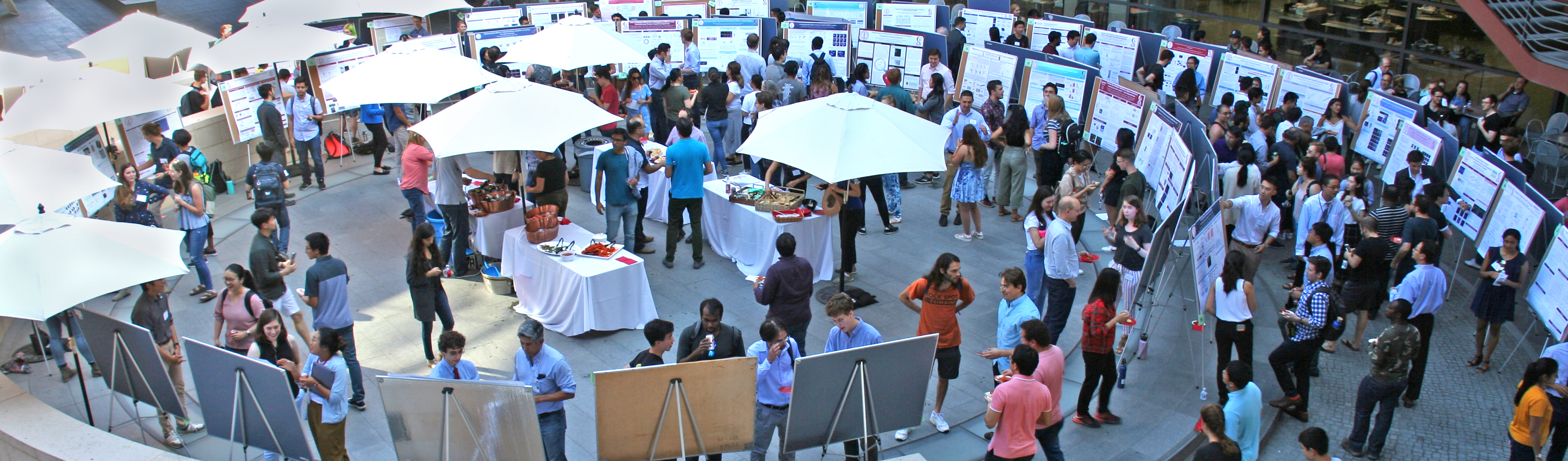 Photo taken from overhead of the Clark Courtyard, with dozens of posters and tables of food being visited by numerous people.