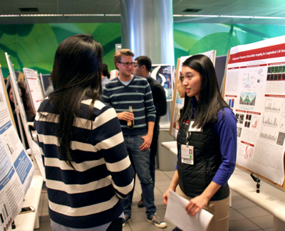 Photo of several diverse individuals conversing at a Stanford Bio-X poster session indoors.