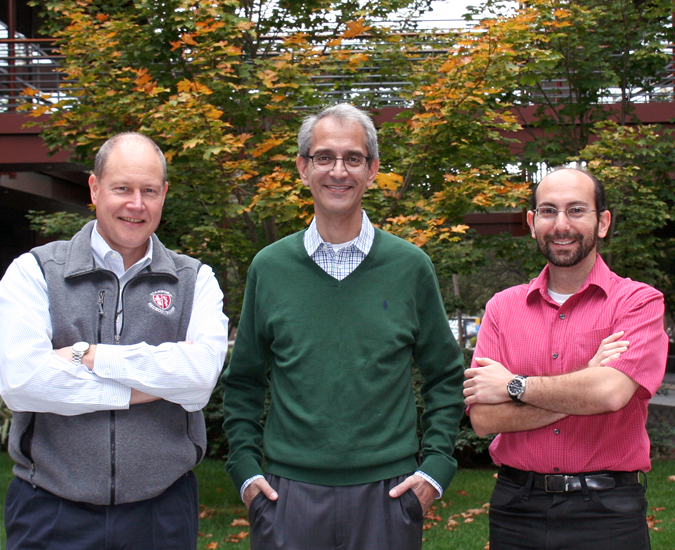 Still photo of white male faculty member and two South Asian male faculty members standing together in the Clark Center Courtyard.