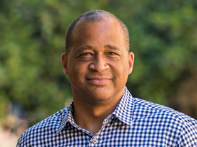 Photo of a Black male faculty member smiling.