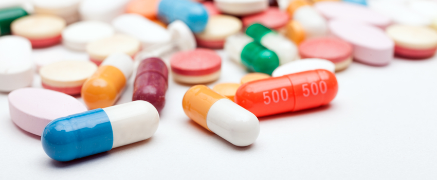 Photo of an assortment of colorful pills spilled across a white surface.