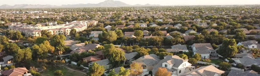 """Overhead view of numerous """"cookie-cutter"""" style houses' roofs."""