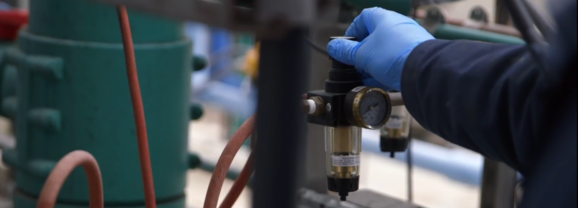 Screenshot/image of a man's hand in a blue glove adjusting a valve on a pipe.