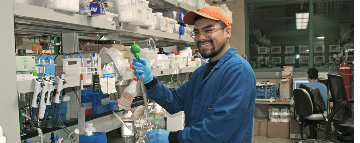 Photo of young Latino male graduate student holding lab equipment in front of a laboratory bench.
