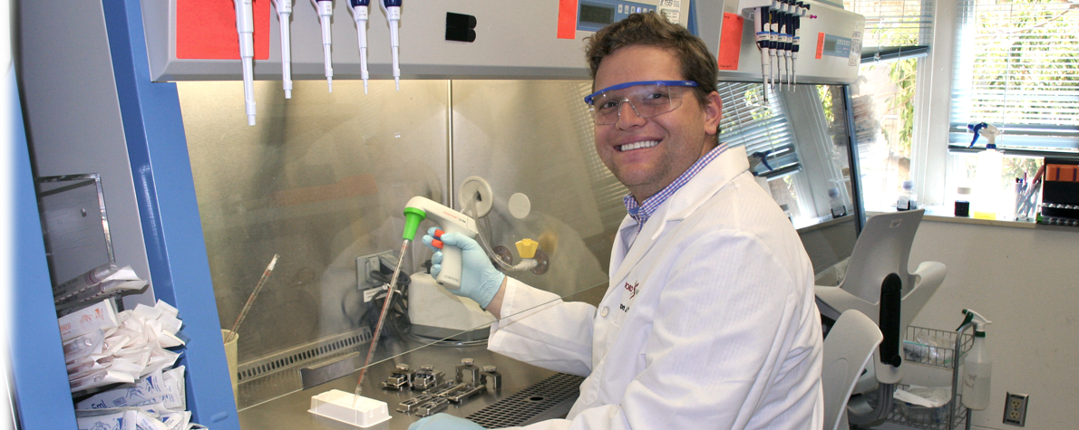 Photo of a smiling male graduate student wearing a white lab coat and other Personal Protection Equipment, sitting at a fume hood and using a pipetting device.