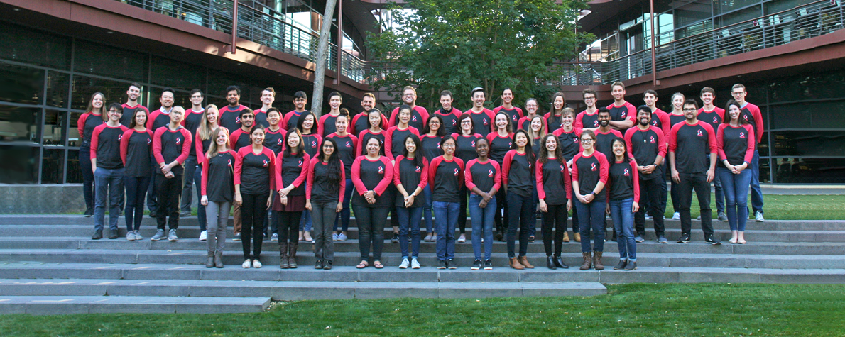 Photo of dozens of Stanford Bio-X PhD Fellows standing together in matching dark gray and red shirts.