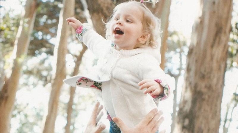 Photo of a man tossing his blonde toddler daughter in the air.