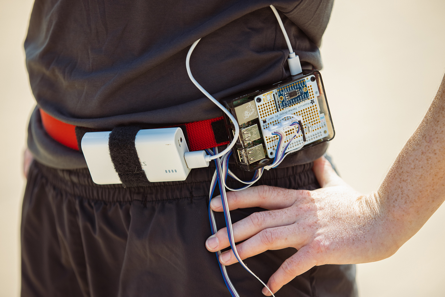 Photo of white female graduate student's hip displaying the circuit board and wires and other components of the wearable measurement device.