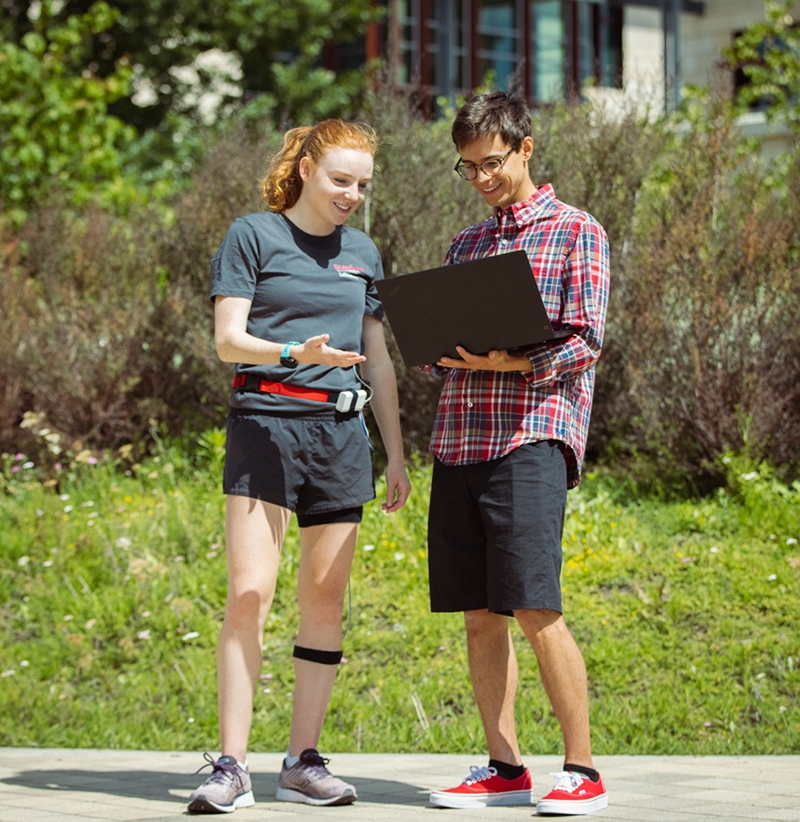 Photo of white female graduate student wearing running clothes and the wearable device looking at laptop held by white male graduate student.