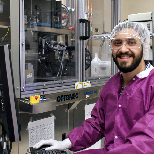 Photo of graduate student Abdul Obaid in the lab, dressed in clean room attire and seated beside a large piece of equipment.
