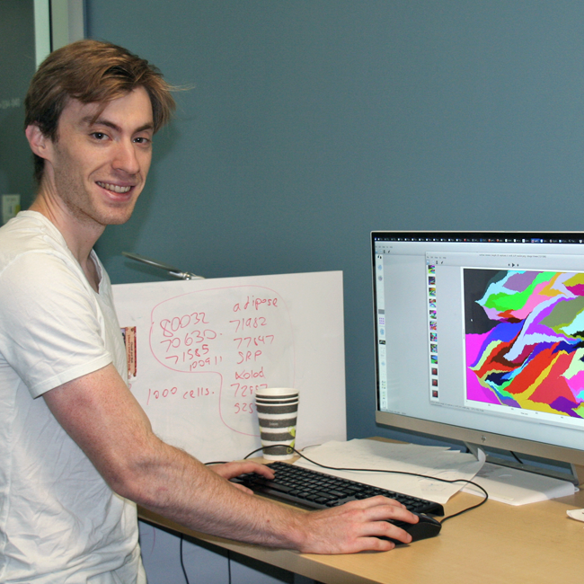 Photo of graduate student Alec Tarashansky in the lab, working at a computer with a colorful display.