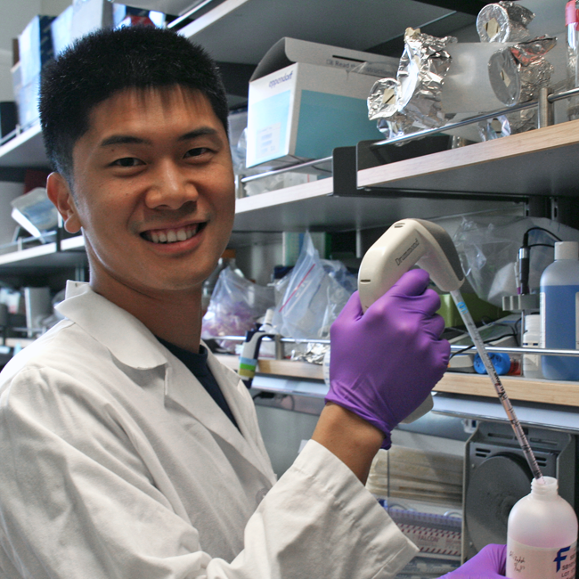 Photo of graduate student Binbin Chen in the lab, pipetting a pink solution.