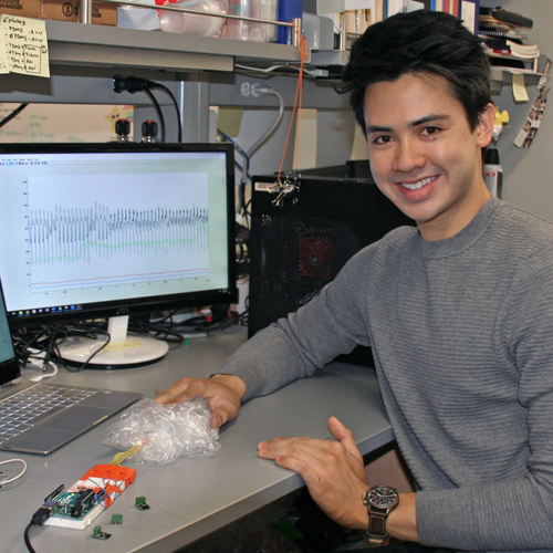 Photo of undergraduate student Cody Carlton sitting at a desk, holding a small device with numerous attachments, which is showing a heartbeat EKG-like reading on a computer monitor behind him.