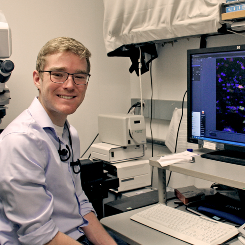 Photo of undergraduate student Jacob Greene sitting in lab space, with microscope behind him and a computer screen showing colorful images of cancer cells in front of him.