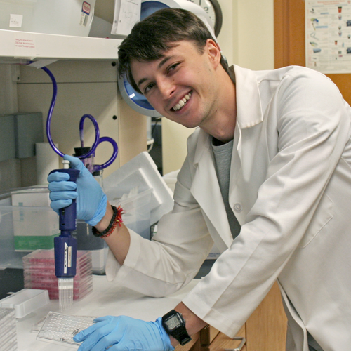 Photo of student Jan Sokol at a lab bench, using a pipette.