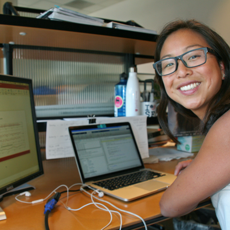 Photo of graduate student Johanna O'Day in the lab, coding on a computer with dual monitors.