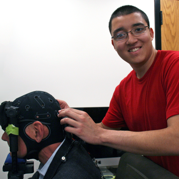 Photo of USRP student Jorge Delgado in the laboratory, having put a piece of monitoring headgear on Dr. Anthony Norcia.