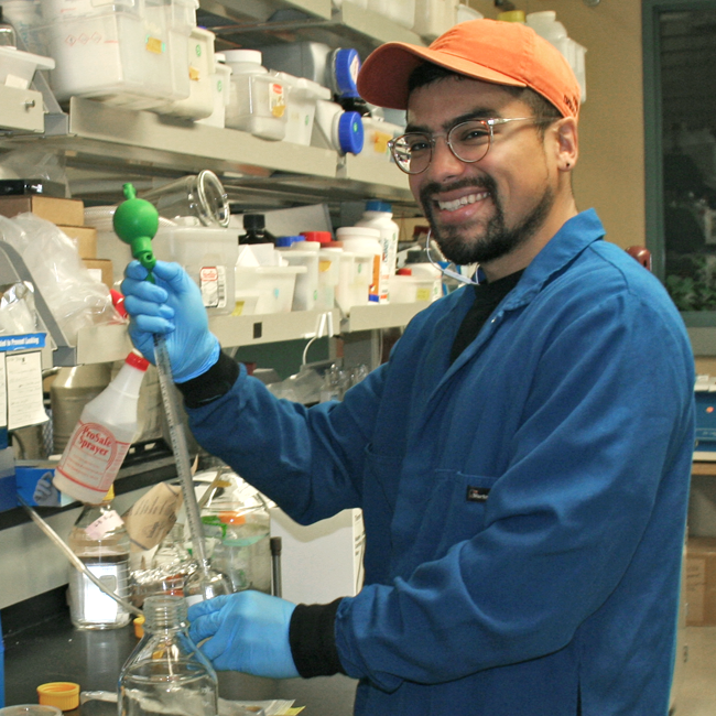 Photo of graduate student Jorge Meraz in the lab, working with a long, tube-shaped device.