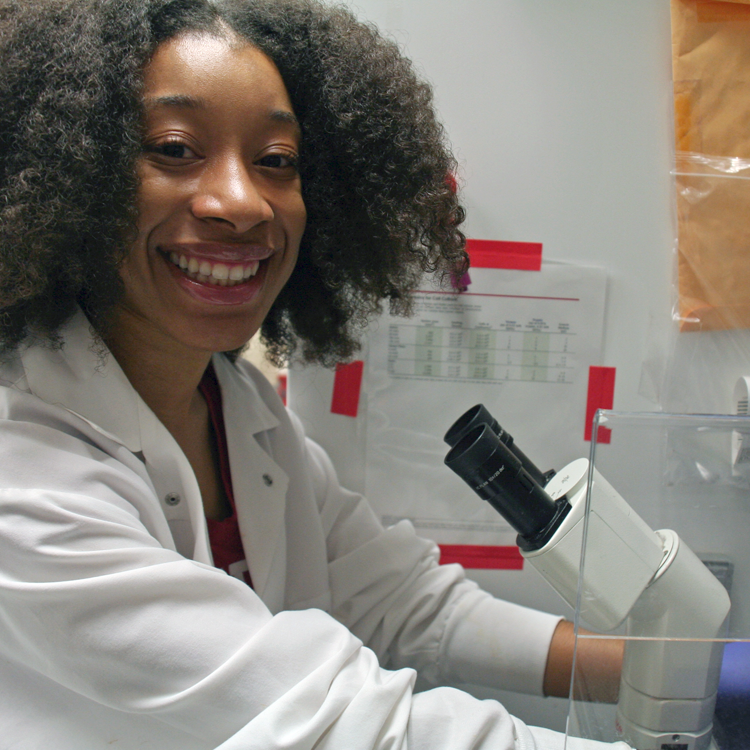 Photo of USRP student Kamina Wilkerson in the lab, using a microscope.
