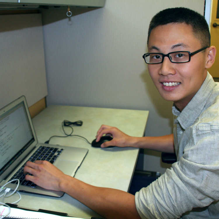 Photo of USRP student Alan Aw in his laboratory, working on a laptop computer.