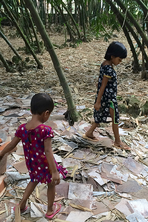 Photo of two young girls wearing brightly-colored dresses walking over a pile of square-shaped scraps of metal.