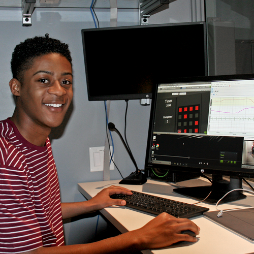 Photo of undergraduate student Marlon Washington II sitting in a dim observation room, with images from a video feed and corresponding data on his computer screen.