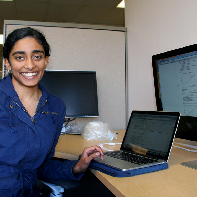Photo of USRP student Maya Varma in the laboratory, showing graphs on two computer screens.