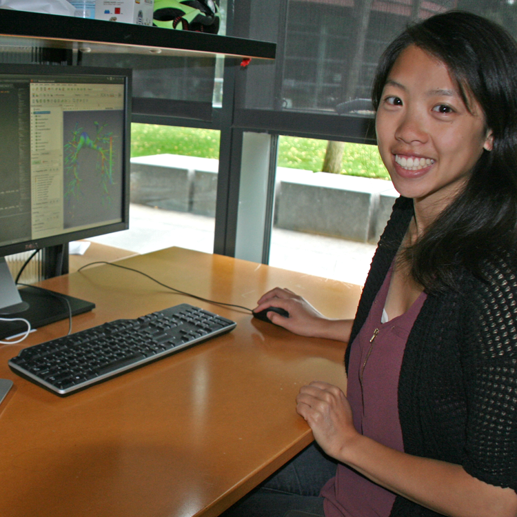 Photo of graduate student Melody Dong in the lab, displaying an image of vasculature models on a computer screen.