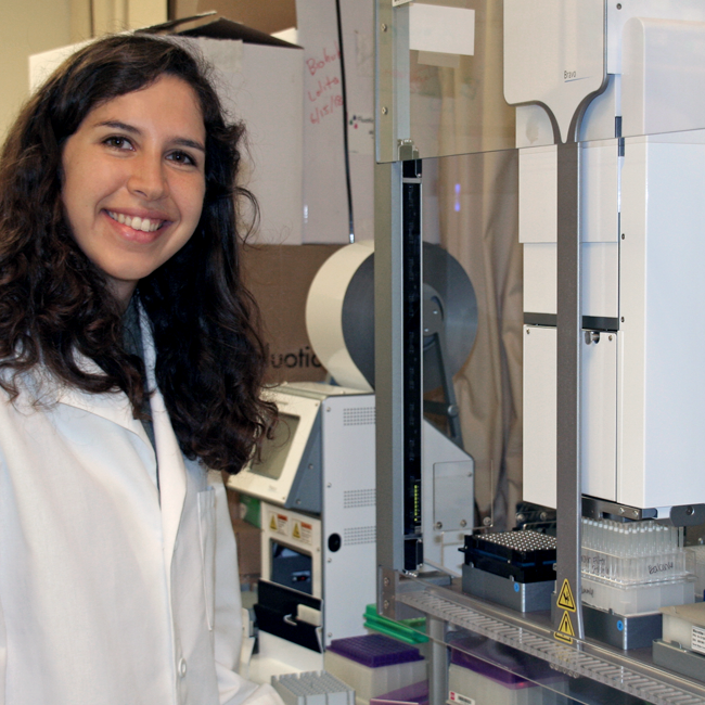 Photo of graduate student Mira Moufarrej in the lab, standing beside a large machine with samples in it.