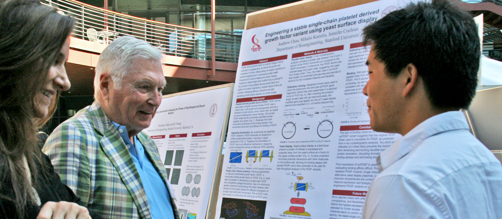 Photo of Pitch Johnson with a young student, standing at the student's scientific poster and smiling during discussion.
