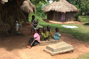 Children in Uganda sit at the graves of two of their siblings buried side by side. Both were likely victims of infectious disease.