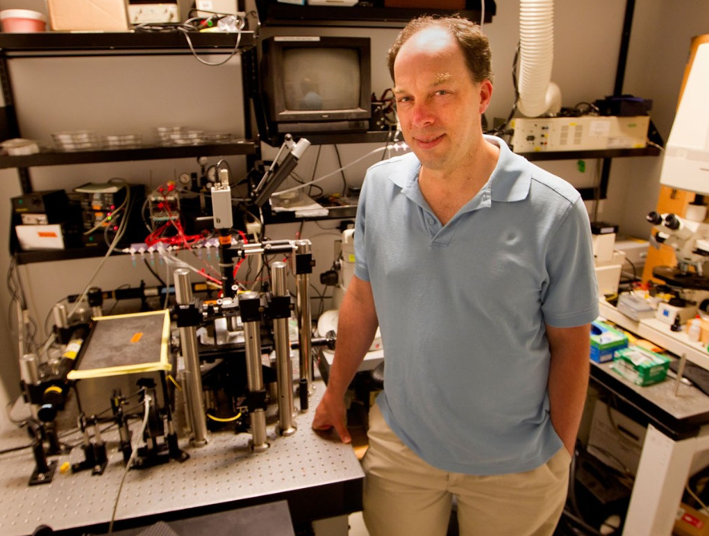 Photo of mid-aged professor in polo shirt standing by advanced lab equipment.