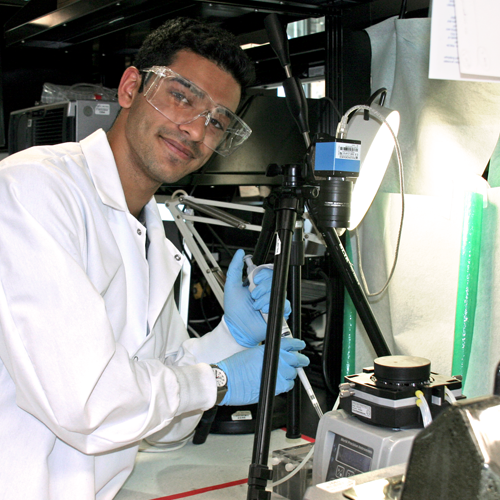 Photo of undergraduate student Rahul Shiv in the lab using a long pipette near several lab equipment devices.