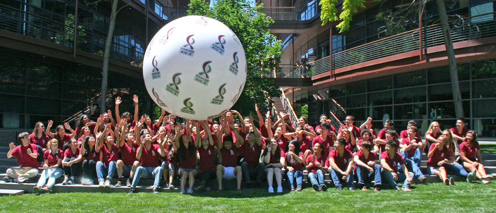 Group photo of 2017 students in red shirts, bouncing a huge white ball with Bio-X logos on its sides.