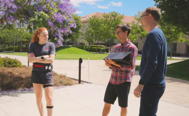 Screenshot of white female graduate student wearing running clothes and the wearable measurement device components, white male graduate student holding a laptop, and white male faculty member standing in an open courtyard area.
