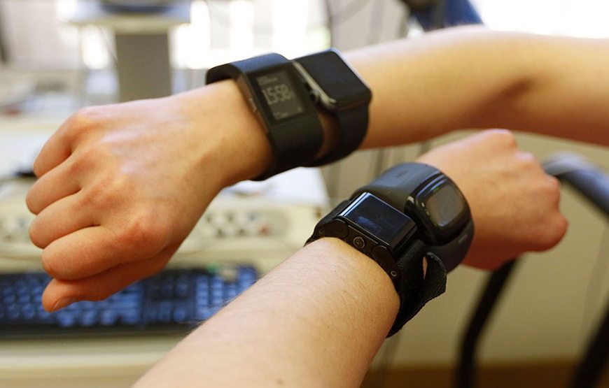Photo of a subject's two hands, with each wrist wearing two wearable sensor devices.