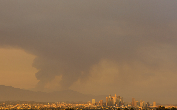 Photo of Los Angeles skyline with huge plumes of smoke in the background, tinting photo yellow.