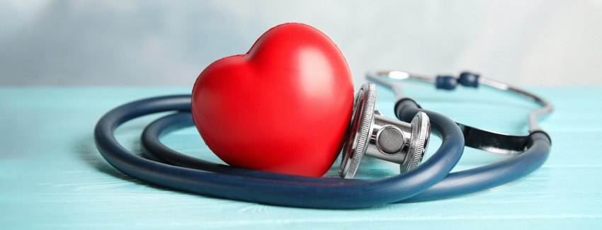Photo of a plastic heart with a stethoscope wrapped around it.