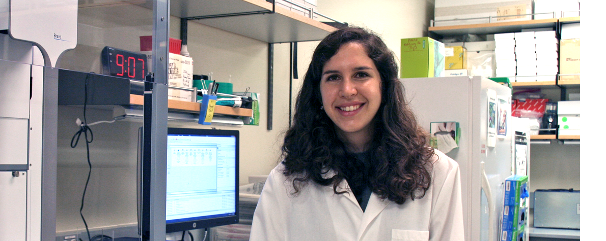 Photo of smiling female graduate student in a wet laboratory.