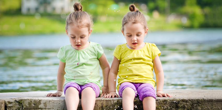 Photo of identical twin toddler-aged girls sitting on a pier with their feet in a lake.