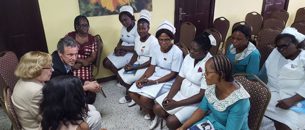 Photo of 3 Stanford faculty seated on left, having a discussion with several Nigerian nurses in uniforms.