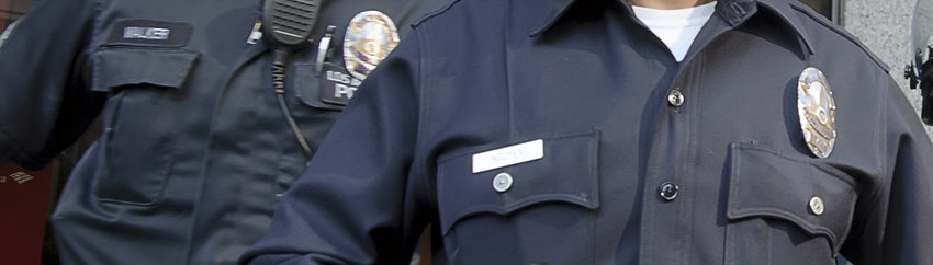 Photo of two police officers, showing the badges and name pins on their uniforms.