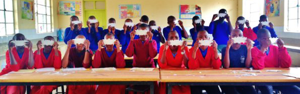 Photo of children in a Ugandan classroom holding up paper Foldscope microscopes.