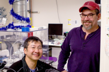 Photo of Dr. Alan Cheng, seated in a wet laboratory area, with Dr. Anthony Ricci standing beside his chair, with both professors smiling at the camera.