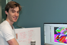 Photo of white male graduate student standing next to a computer displaying colorful data on a large screen.